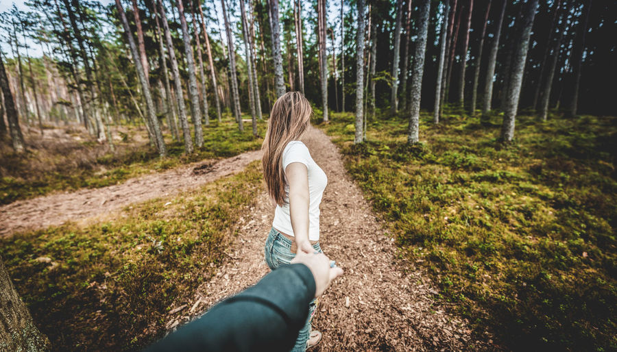 Close-up of woman holding hand in forest