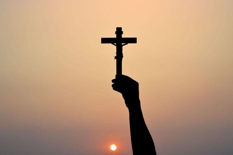 Silhouette cross against sky during sunset