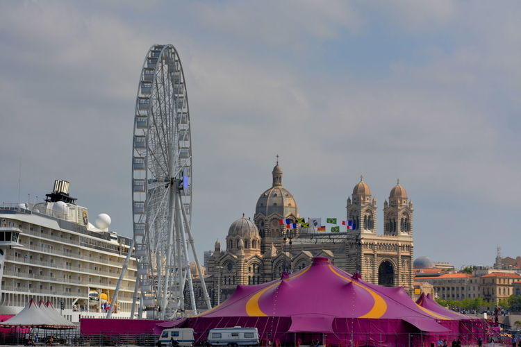 Low angle view of ferris wheel against buildings in city