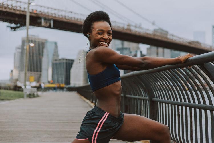 Woman exercising on bridge in city