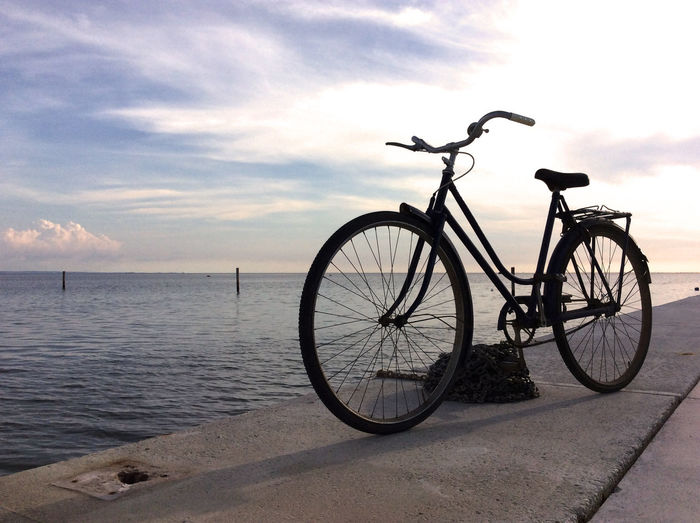 Bicycle on jetty against sea