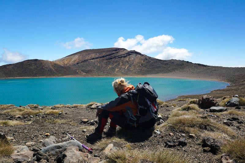 Backpacker sitting at lakeshore against sky