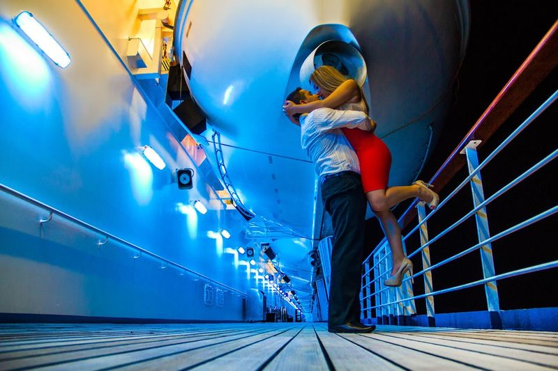 Side View Full Length Of Man Lifting Woman In Cruise Ship At Night
