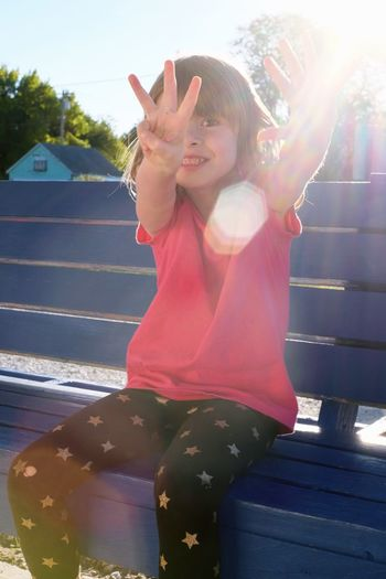 Cute Smiling Girl Gesturing On Bench During Sunny Day