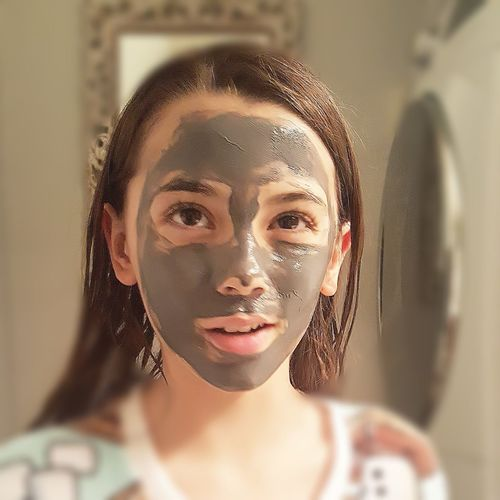 Close-Up Of Girl Wearing Face Mask At Home