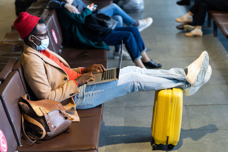 Young businessman wearing mask using laptop while sitting at airport