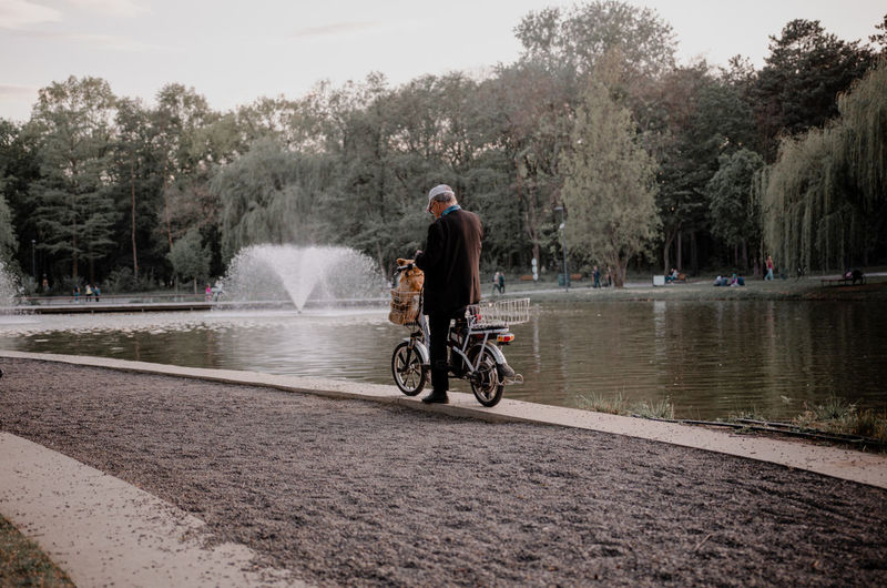 Rear view of man riding bicycle on water