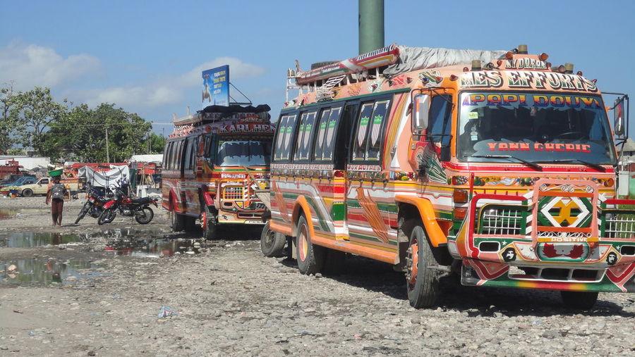 Buses on field against sky