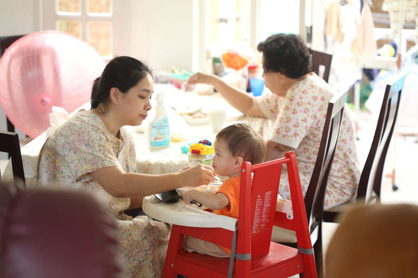 Adult Bonding Cheerful Child Community Outreach Day Eat Education Family Females Girls Happiness Home Caregiver Indoors  Lifestyles Meal Mid Adult Mother People Smiling Son Togetherness Women
