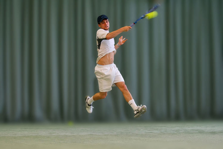 Fast Athletic Tennis Tennis Ball Tennis Sport Athlete Ball Dynamic Forehand Hitting Jumping Leisure Activity Motion One Person Player Playing Racket Sport Sportsman Strong Tennis Court Tennisplayer Vitality Young Adult Young Men