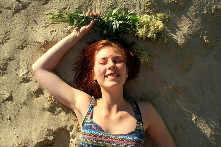 Directly Above Shot Of Happy Young Woman Holding Plants While Lying On Sand At Beach