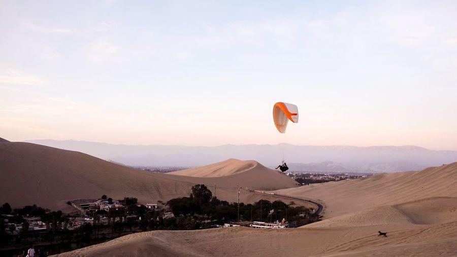 Parapendio flying over desert against sky