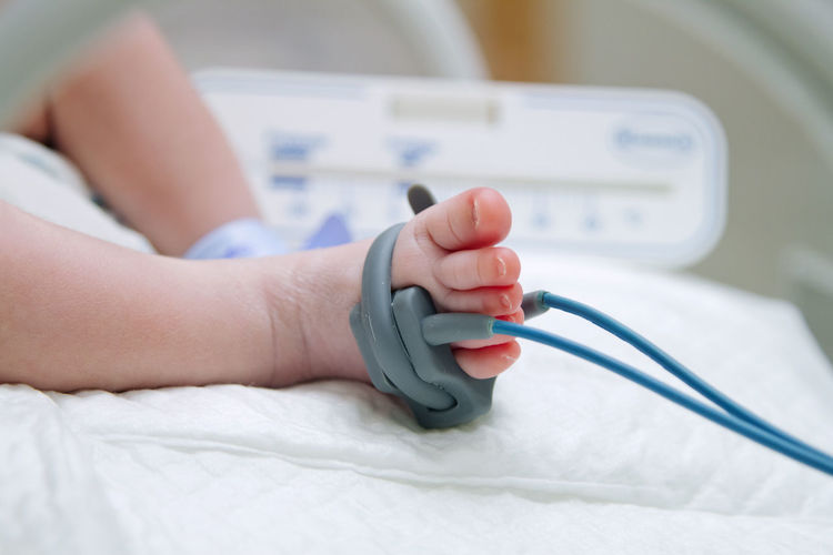 Low Section Of Baby With Medical Equipment On Bed