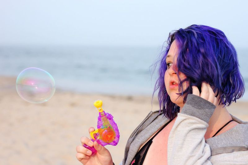 Beautiful woman shooting a single bubble out of a toy gun Beautiful Stunning Toy Bubble Gun One Person Women Nature Land Hair Blowing Beach Leisure Activity Bubble Focus On Foreground Sea Vulnerability  Holding Day Adult Outdoors Real People Hairstyle