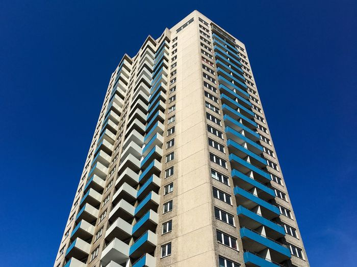 Low Angle View Of Tall Buildings Against Blue Sky