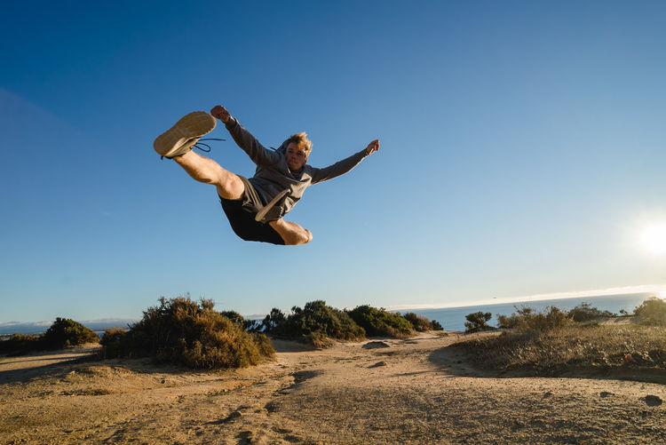 Young Man Jumping Against Clear Sky