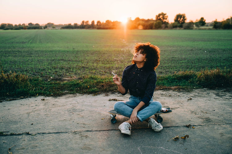 Teenage girl sitting on skateboard against clear sky during sunset