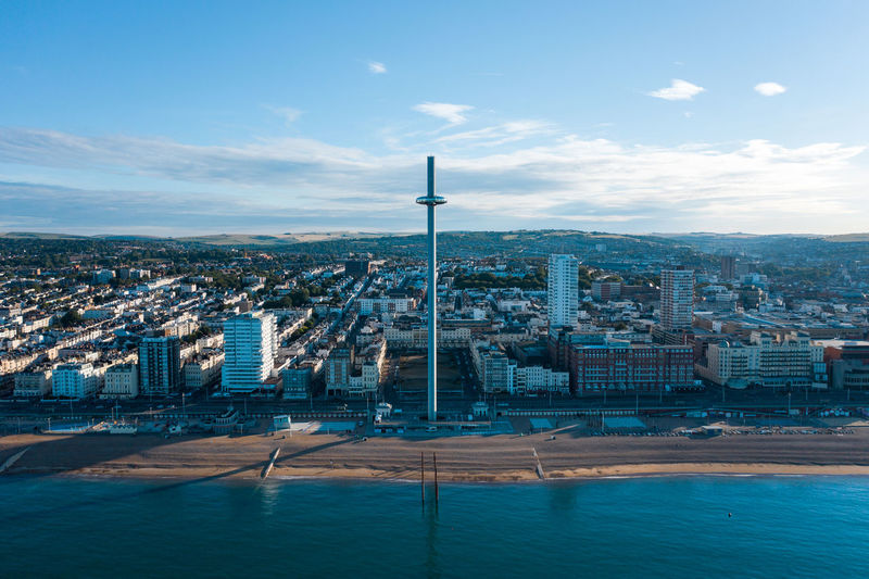 Aerial shot of brighton with the i360 and beach in the morning light with wispy cloud and blue sky
