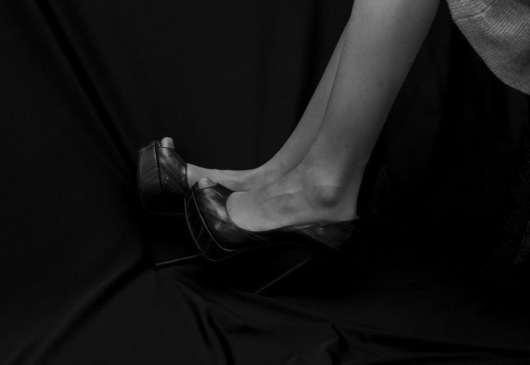 Low section of woman wearing high heels against black background