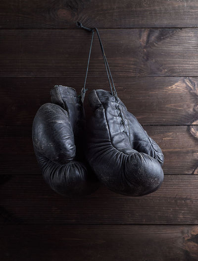 Close-Up Of Boxing Gloves Hanging On Wooden Wall