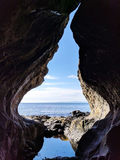 Scenic view of sea seen through rock formations