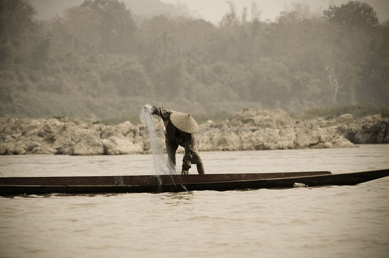 Fisherman pulling net while standing on boat in river