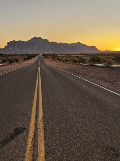 Empty road along landscape at sunrise
