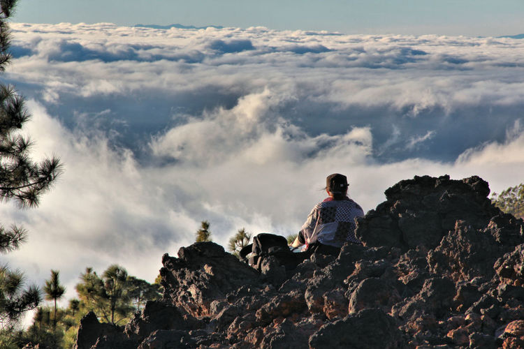 Rear View Of Person Sitting On Mountain Against Cloudscape
