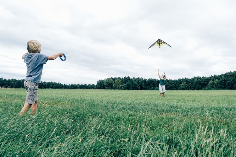 Bavaria Series / Kite Agriculture Boys Casual Clothing Childhood Cloud - Sky Day Field Flying Full Length Grass Growth Kite - Toy Leisure Activity Mid-air Nature One Person Outdoors Real People Rear View Scarecrow Sky Tree