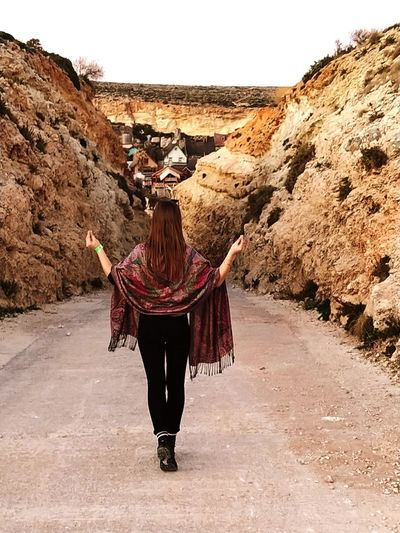 Rear view of young woman with scarf walking on road
