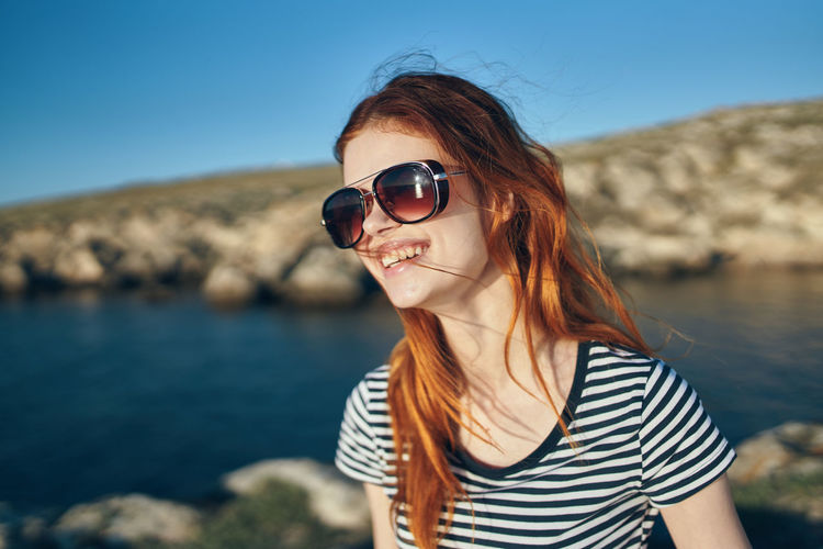 Portrait of young woman wearing sunglasses against sea
