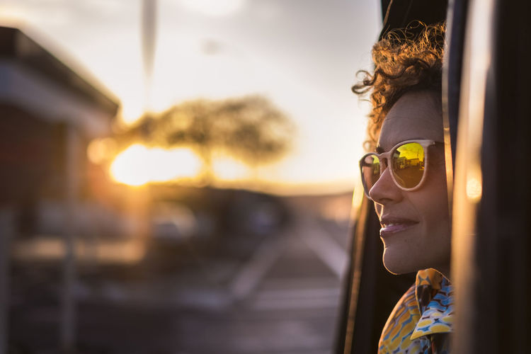 Smiling woman wearing sunglasses while traveling in vehicle