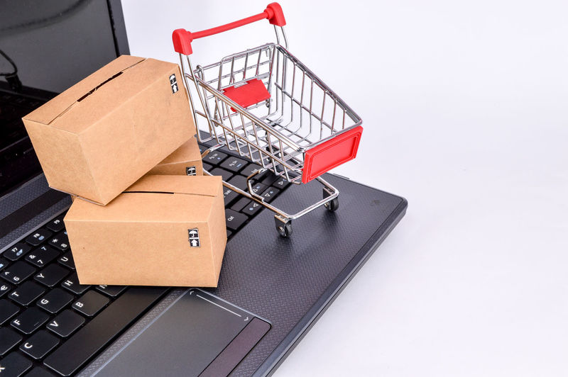 Close up of laptop with shopping cart and cardboard boxes over white background