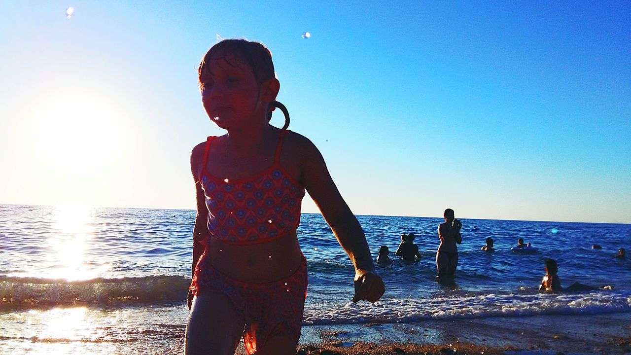 sea, water, horizon over water, real people, sky, standing, nature, one person, lifestyles, sunlight, clear sky, outdoors, beauty in nature, beach, leisure activity, vacations, scenics, childhood, weekend activities, boys, day, young adult, people