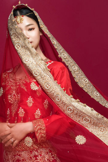 Portrait of beautiful young bride standing against red background