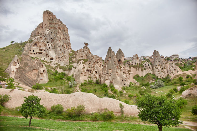 View of rock formations on landscape against cloudy sky