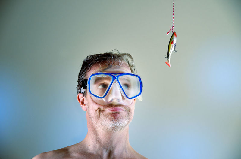 Shirtless Man Wearing Swimming Goggles While Looking At Hanging Fish