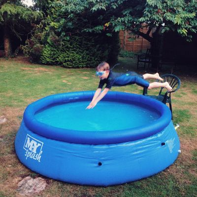 Boy jumping into a garden swimming pool Water Swimming Pool Real People Childhood Leisure Activity Full Length Playing Inflatable  One Person Outdoors Tree Day Seven Years Old fun Fun Mid-air Hampshire  Water Park People