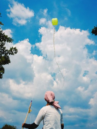 Rear View Of Person Flying Kite