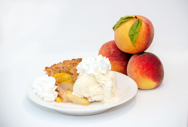 sweet peach cobbler with ice cream and whipped cream Agriculture Dessert Fresh Produce Hello World Ice Nature Orange Summertime USA Vitamins Food Fresh Fruit Juicy Just Picked Michigan Peaches Organic Peach Peach Cobbler Peaches Produce Sweet Tasty White Background Yellow