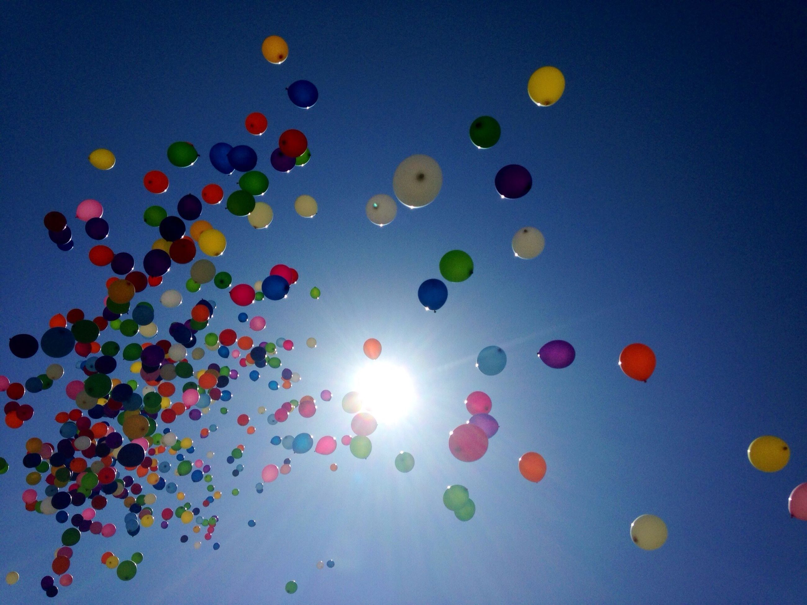 multi colored, mid-air, balloon, low angle view, blue, flying, sky, lens flare, colorful, clear sky, sun, hot air balloon, beauty in nature, no people, nature, outdoors, circle, large group of objects, scenics, copy space