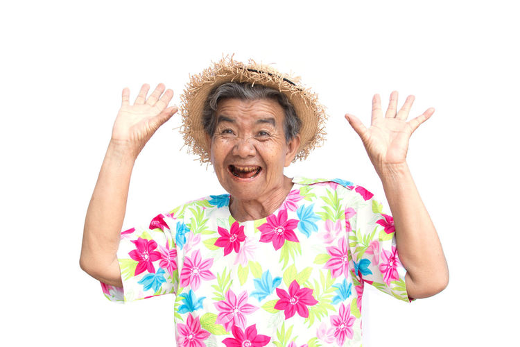Portrait Of Happy Senior Woman Standing Against White Background