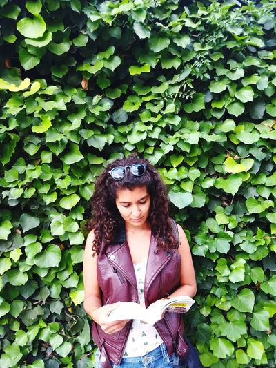 Woman Reading Book While Standing Against Plants