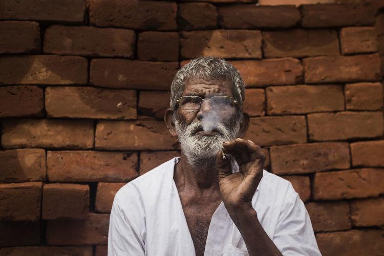 Portrait of man wearing brick wall