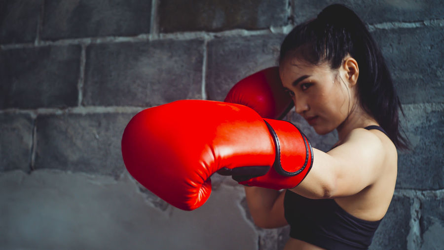beautiful,body,boxer,boxing,calorie,care,champion,coach,competition,concept,confidence,confident,defense,energy,exercise,female,fight,fighter,fit,fitness,girl,gloves,gym,health,healthy,human,kickboxing,lifestyle,martial,modern,muscular,portrait,power,pretty,sexy,shape,sport,sportsmen,strength,strong,success,sweat,sweating,training,victory,vitality,wellness,winner,women,yoga Boxing - Sport One Person Lifestyles Strength Real People Boxing Glove Sport Red Young Adult Standing Wall - Building Feature Indoors  Young Women Women Adult Punching Exercising Leisure Activity Hairstyle