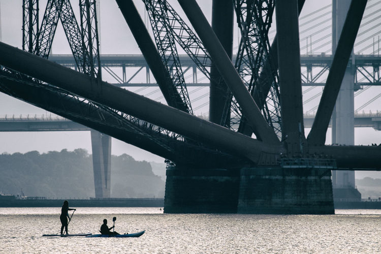 People on paddleboarding by bridge at river