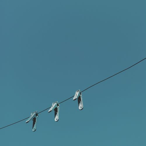 Low angle view of clothespin on clothesline against clear blue sky