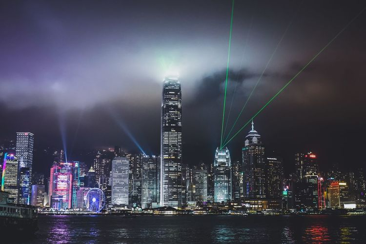 Illuminated Cityscape By River Against Cloudy Sky At Night