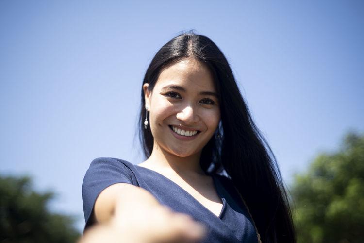 Portrait of a smiling young woman against blue sky