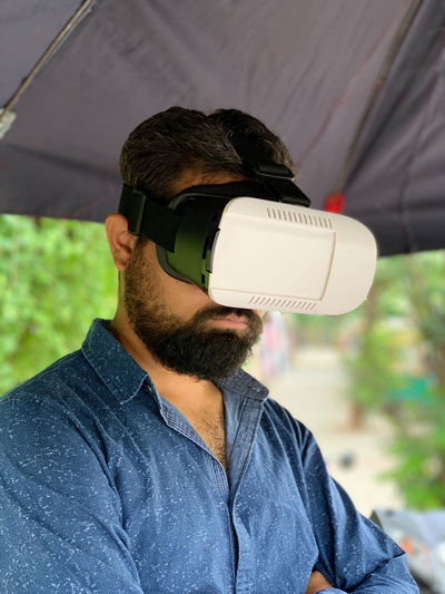 Man using VR headset One Person Real People Young Men Casual Clothing Men Leisure Activity Facial Hair Beard Lifestyles Young Adult Focus On Foreground Glasses Front View Technology Headshot Portrait Day Sunglasses Males